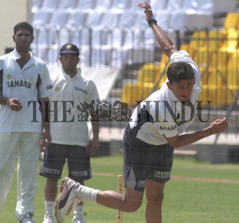 India's Ajit Agarkar completes his bowling action, watched